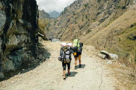 Porter and Sherpa walking with big bag baggage luggage in Himalaya Mountains in Nepal. Khumbu glacier in Everest National Park and people trekking on rocky footpath trail. Banco de Imagens