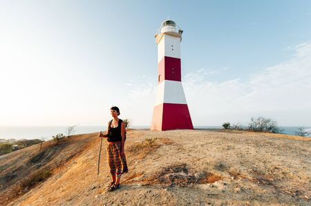 girl stands next to the lighthouse in mancora