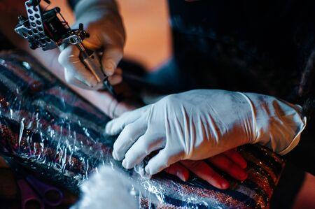 Tattoo artist doing tattoo in tatoo salon. Zdjęcie Seryjne
