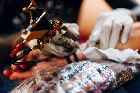 Tattoo artist doing tattoo in tatoo salon. Stock fotó