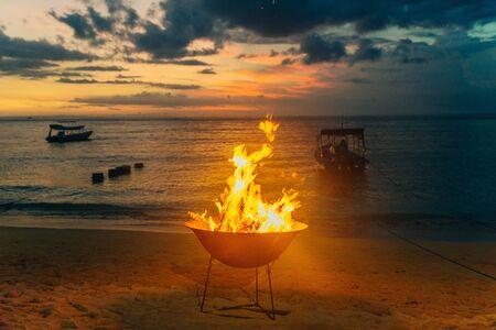 Burning fire on the beach - sunset background Фото со стока