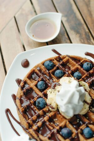 Plate of belgian waffles with ice cream, chocolate sauce and fresh blueberries
