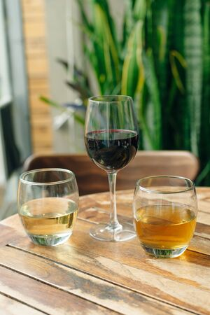 Glass of white and red wine on vintage wooden table in restaurant