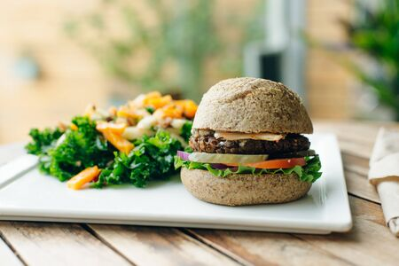 Vegan big burger with salad and piclkes in classic bun, served on white plate. Homemade healthy fast food.