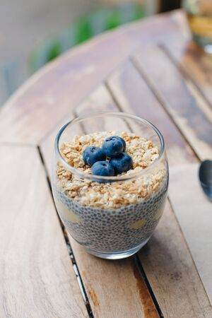 blueberry yogurt parfait with granola, oats and chia seeds in a glass on white wooden table 版權商用圖片