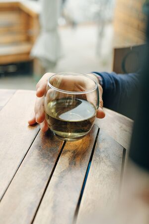 Glass of white wine on vintage wooden table in restaurant