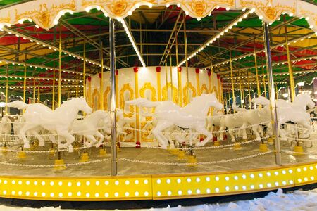 Carousel. A white luxury Merry-go-round at the winter fair, only temporary event fair organized for Christmas and New Year at night