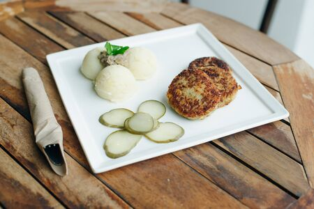 vegetarian cutlets with mashed potatoes and pickles on wooden table