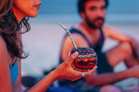 Young woman drinking traditional Argentinian yerba mate tea from a calabash gourd with bombilla stick