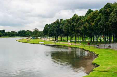 View of lake, trees and mountains in Simon Bolivar Metropolitan public park in the middle of Bogota, Colombia