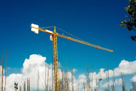 Yellow Industrial Cranes Working on Construction Site Against Blue Sky.