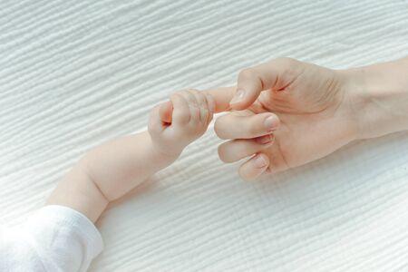 Newborn children's hand in mother hand. Mom and her Child.