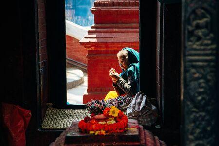 Kathmandu, Nepal - March 2019 woman sits on the territory at Pashupatinath temple