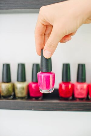 girl holds nail polish on the background of nail polishes.