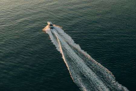 Aerial view of the boat in clear blue water at sunset in summer. Vancouver, canada.