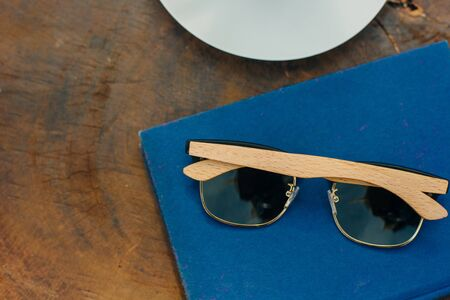 wood sunglasses on a table with a blue book and a cup of coffee Stock Photo