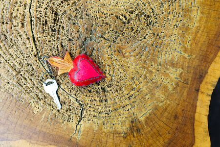 key with a heart-shaped label keychain lies on a wooden Board.