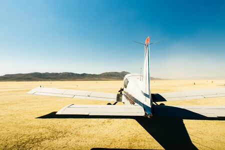 Small airplane in the desert with a blue sky and the sert all around, usa. 免版税图像
