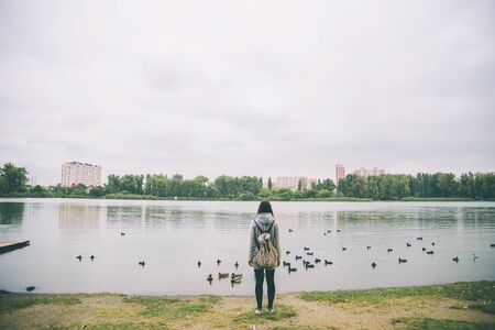 a teenager girl looking at ducks at the lake.