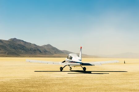 Small airplane in the desert with a blue sky and the sert all around, usa.