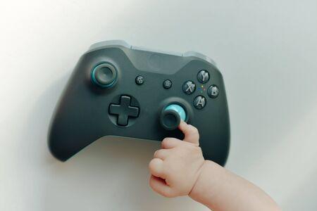 a very small child plays with the joystick Zdjęcie Seryjne