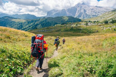 Group hiking in the mountains with large backpacks. Russia.
