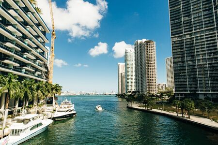 Downtown Miami along the Miami River inlet with Brickell Key in the background and yacht cruising by