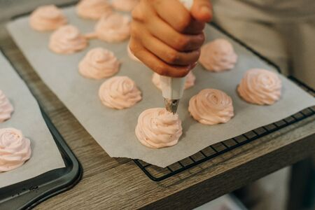 Homemade pink marshmallows on baking paper background on the kitchen.