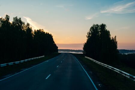 Sun Rising Above Asphalt Open Road In Sunny Sunrise Morning. 版權商用圖片