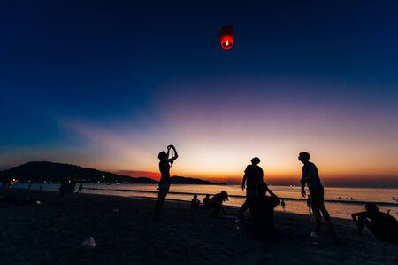 Silhouettes of people on the beach. Launching rice paper hot air balloons in the sky at sunset on a beach in Thailand.