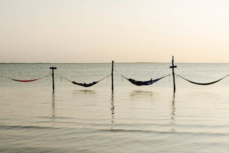 Relaxing in a hammock over the water, Isla Holbox, Mexico. Reklamní fotografie - 148277014