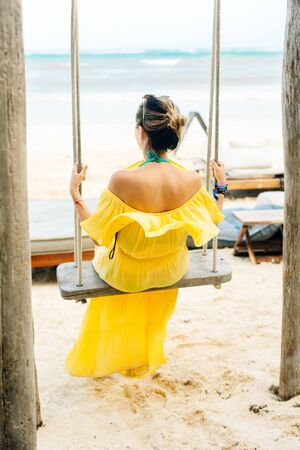 girl in a yellow dress swinging on a swing with his back on the beach. Standard-Bild