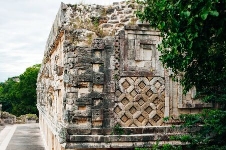 Ancient mayan wall with arches with green garden around in Uxmal, Mexico.