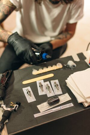 Tattoo artist workplace with machine and bottles with black tattoo ink. 免版税图像