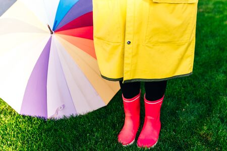 Rainy autumn. Rubber pink boots against. Conceptual image of legs in boots on green grass 免版税图像