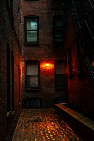 A dark creepy narrow boston alley at night.