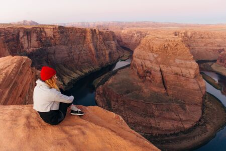 blonde girl sitting Horseshoe Bend in Glen Canyon National Recreation Area in early dawn.