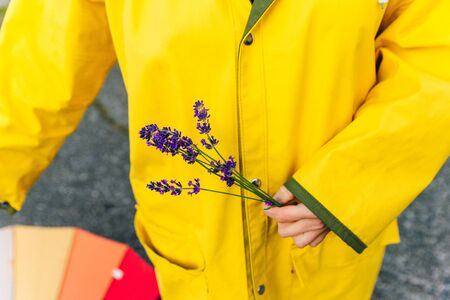 girl in a yellow raincoat holds lavender stalks in her hands. autumn.