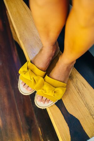 legs of a girl in yellow shoes on a wooden floor. Archivio Fotografico