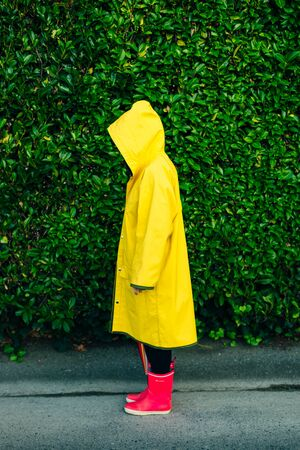 girl in a yellow raincoat on a background of a wall with grass.