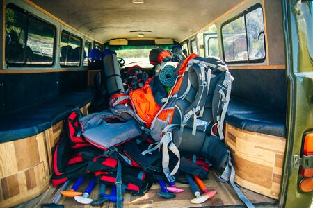 Car trunk with backpacks, karemat and luggage. Travel concept.