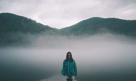 girl in a shirt and glasses stands in the fog on the river.