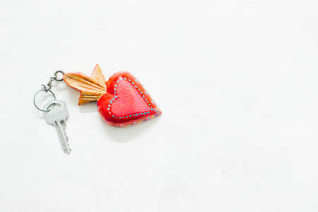 key holding a heart-shaped sign on a white background.