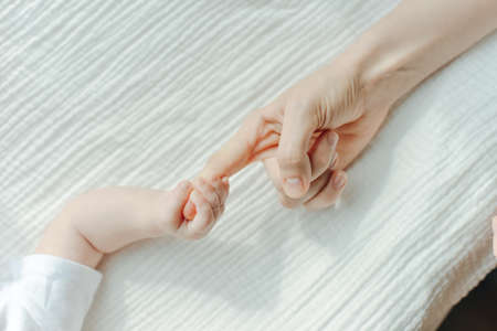 Newborn children's hand in mother hand. Mom and her Child.