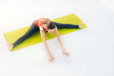 Side view portrait of beautiful young woman doing yoga or pilates exercise. 스톡 콘텐츠