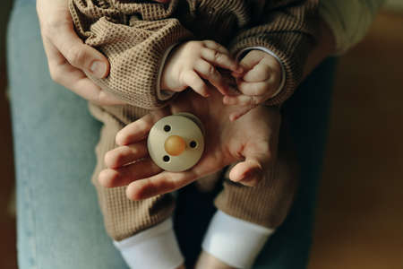 baby holds a pacifier in his mother arms. Reklamní fotografie
