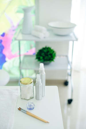 accessories for pedicure brushes and gels with towels and a container in the background. Imagens
