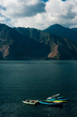 Lake Atitlan Boats in Guatemala with volcano in the background.