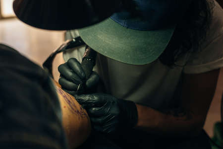 Close up of professional tattooer artist doing picture on hand of man by machine black ink from a jar. Tattoo art on body Stock fotó