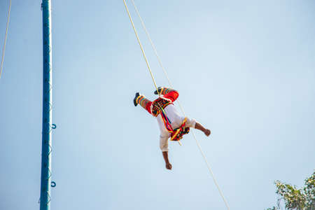 RIVIERA MAYA, MEXICO - DECEMBER, 2019:The Voladores, or flyers performance. They climb up a very high pole their waist to ropes wound around the pole and then jump off.